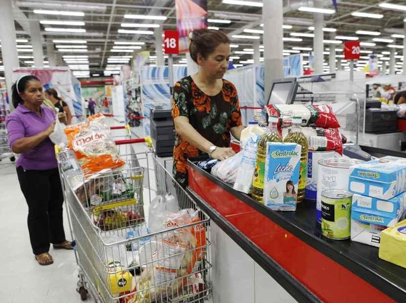 Venezolanas compran en un supermercado.